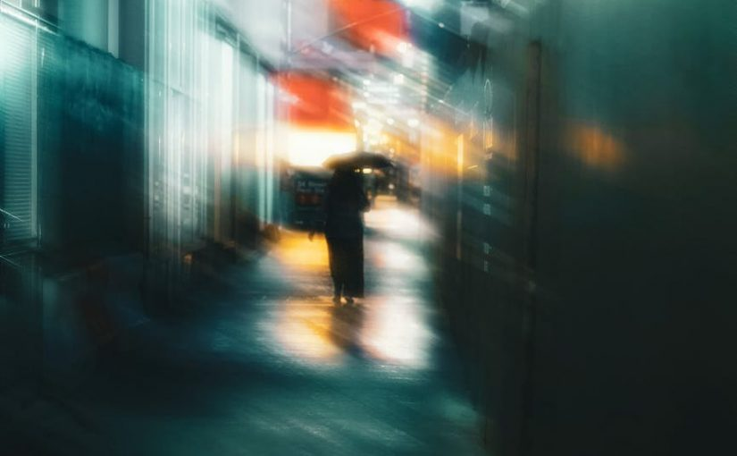 silhouette of unrecognizable woman walking on night street with umbrella
